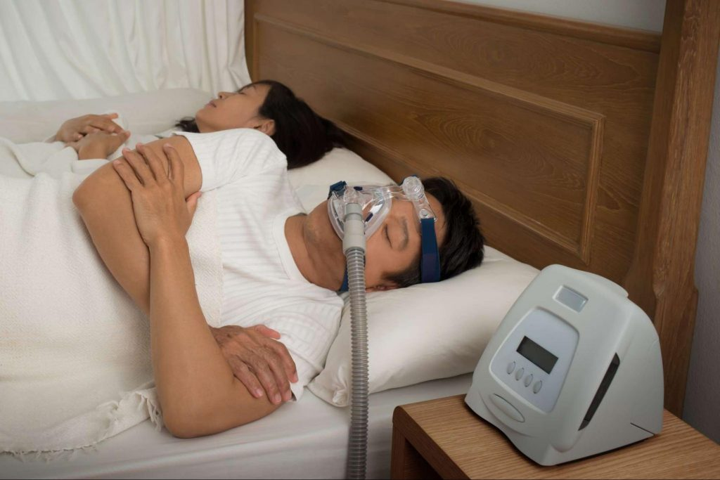 a man sleeping with cpap machine