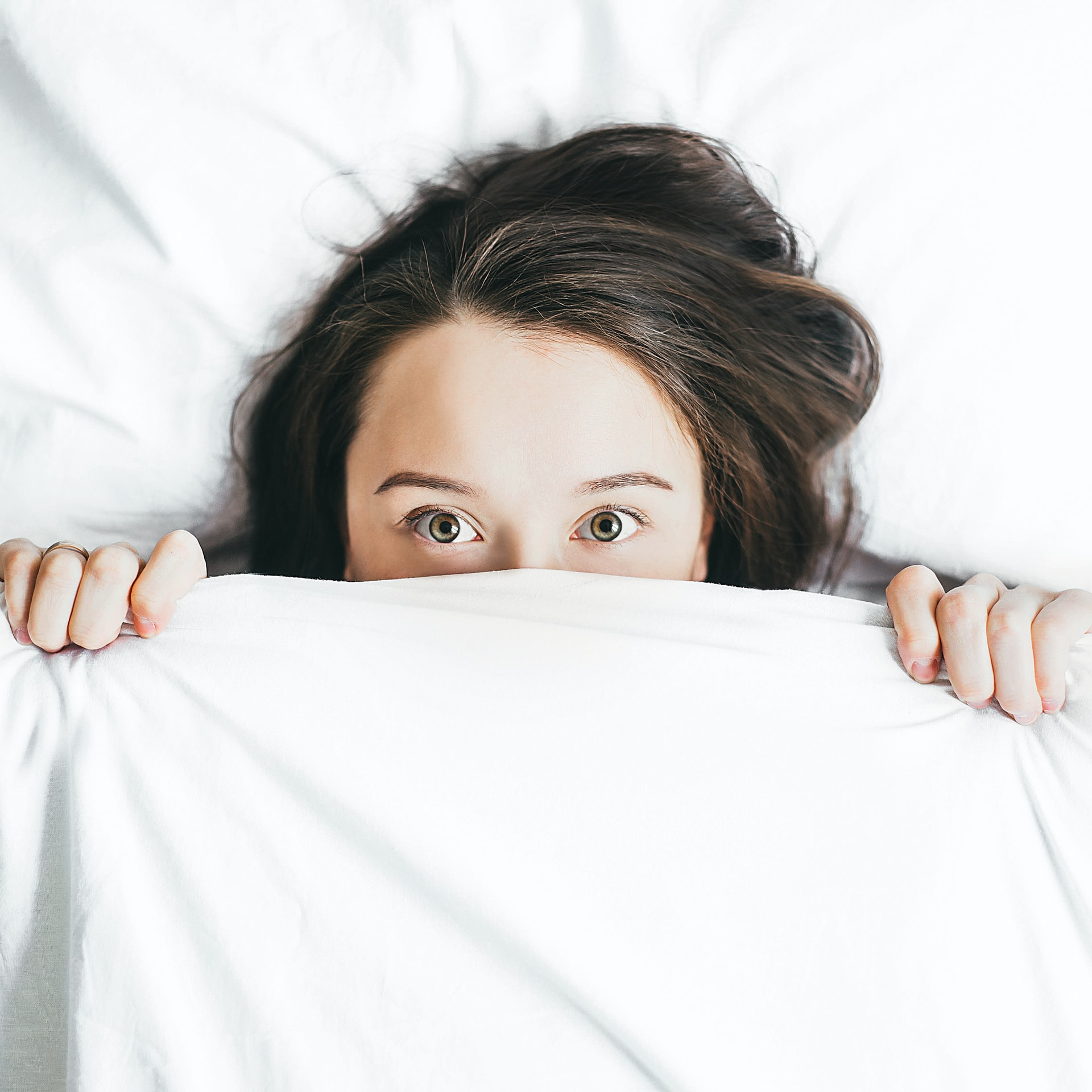 girl trying to cover face with white bedsheet